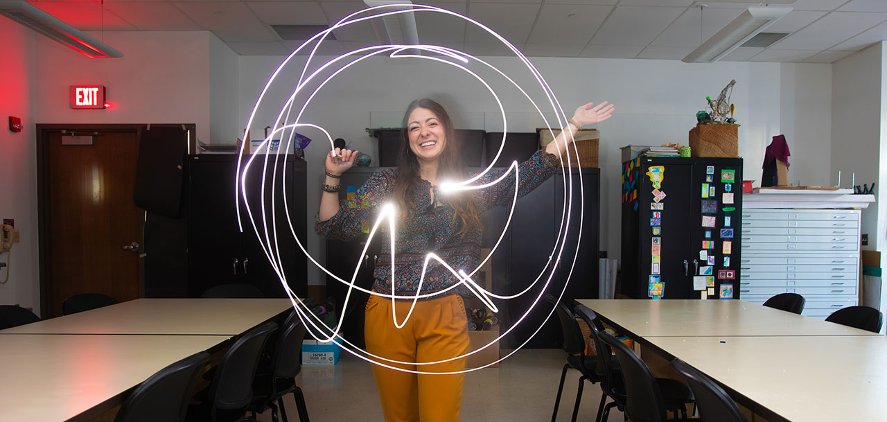 Female student in classroom, using light pen to create pattern.