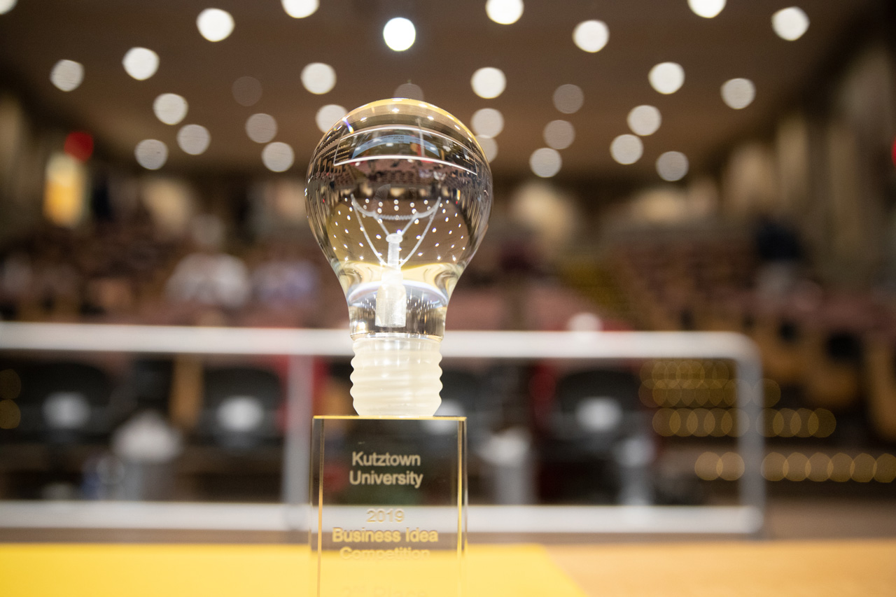 "A clear glass lightbulb trophy with ""1st Place Business Idea Competition"" engraved on it."