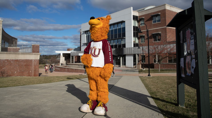 Avalanche the mascot standing in front of the arts building on a sunny day with his face to the sky