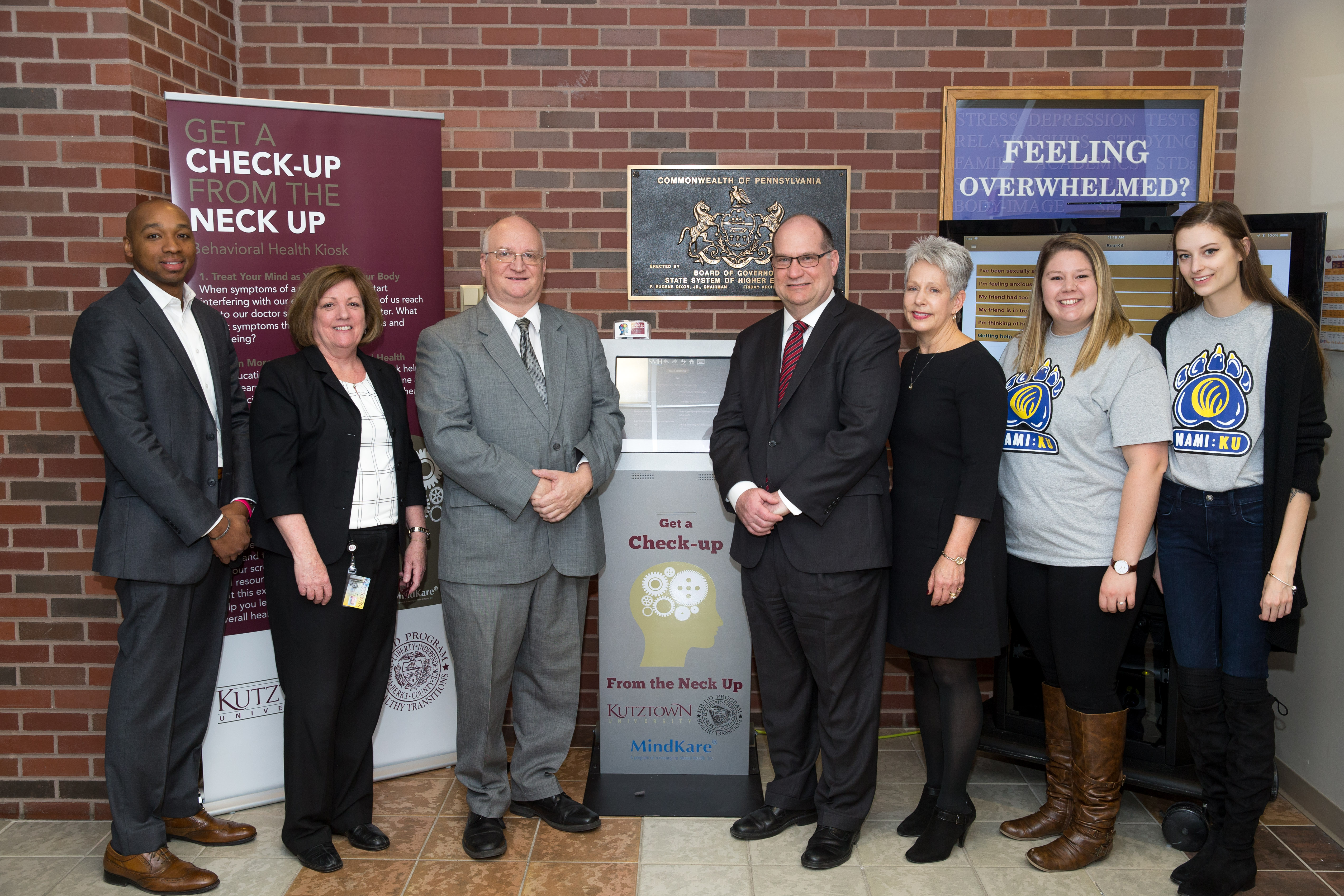 President Hawkinson, Staff, and Students standing on either side of the MindKare mental health kiosk