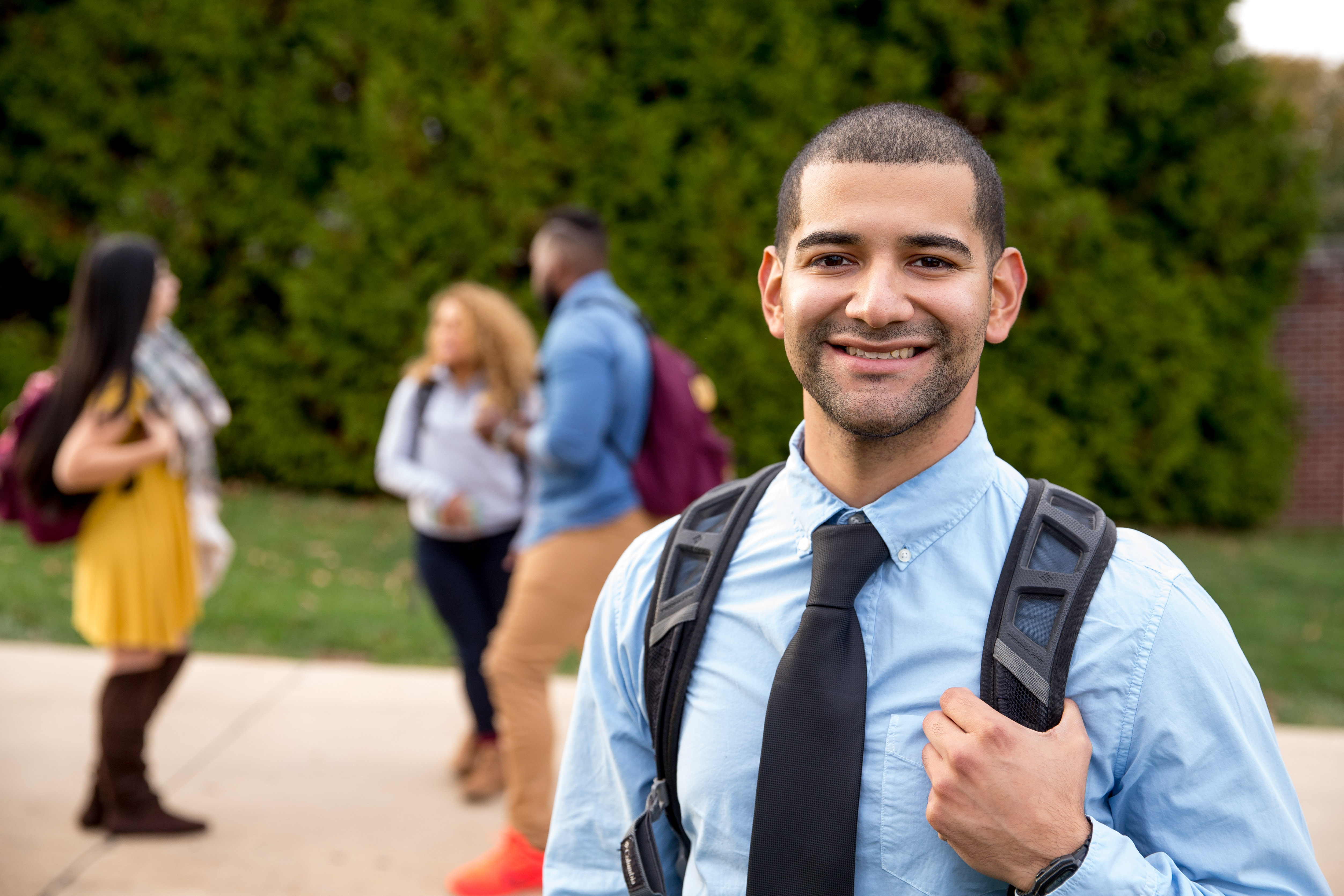 Latino male student smiling on campus with his friends in the background