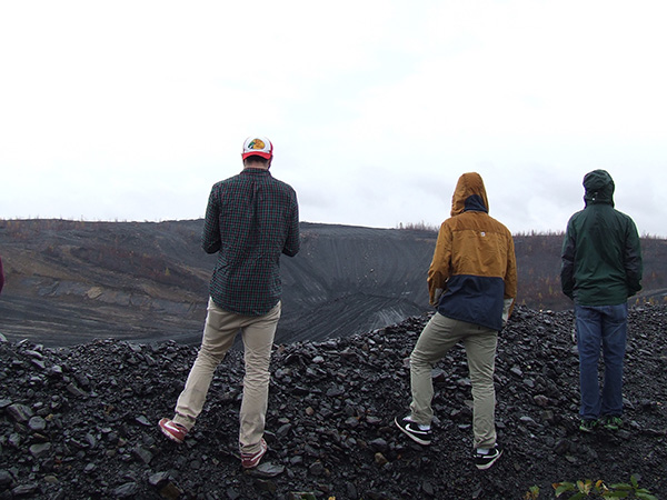 students standing on a waste coal pile with cloudy skies