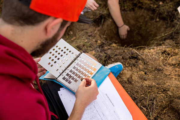 student wearing red sweatshirt and orange cap looking through Monsell soil chart with soil pit in background