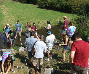 many students working in a stream bed