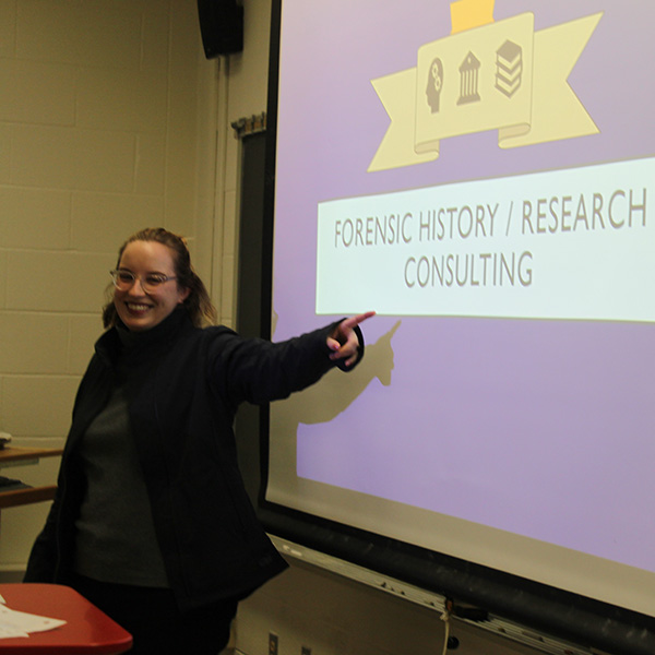 "Lilly giving a presentation, the presentation screen reads: ""Forensic History/Research Consulting"""