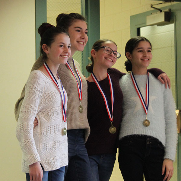 Four middle school girls wearing medals