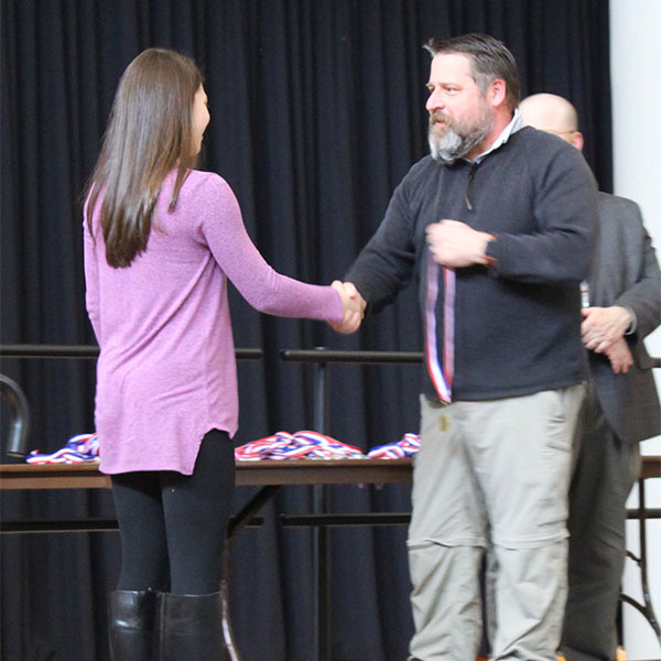 Middle school girl student receiving medal from Dr. Johnson