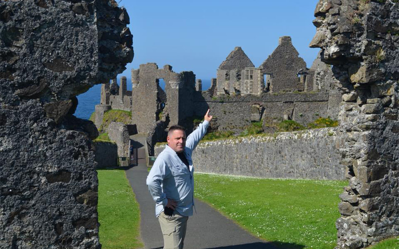 Dr. Johnson pointing to ancient ruins in Ireland