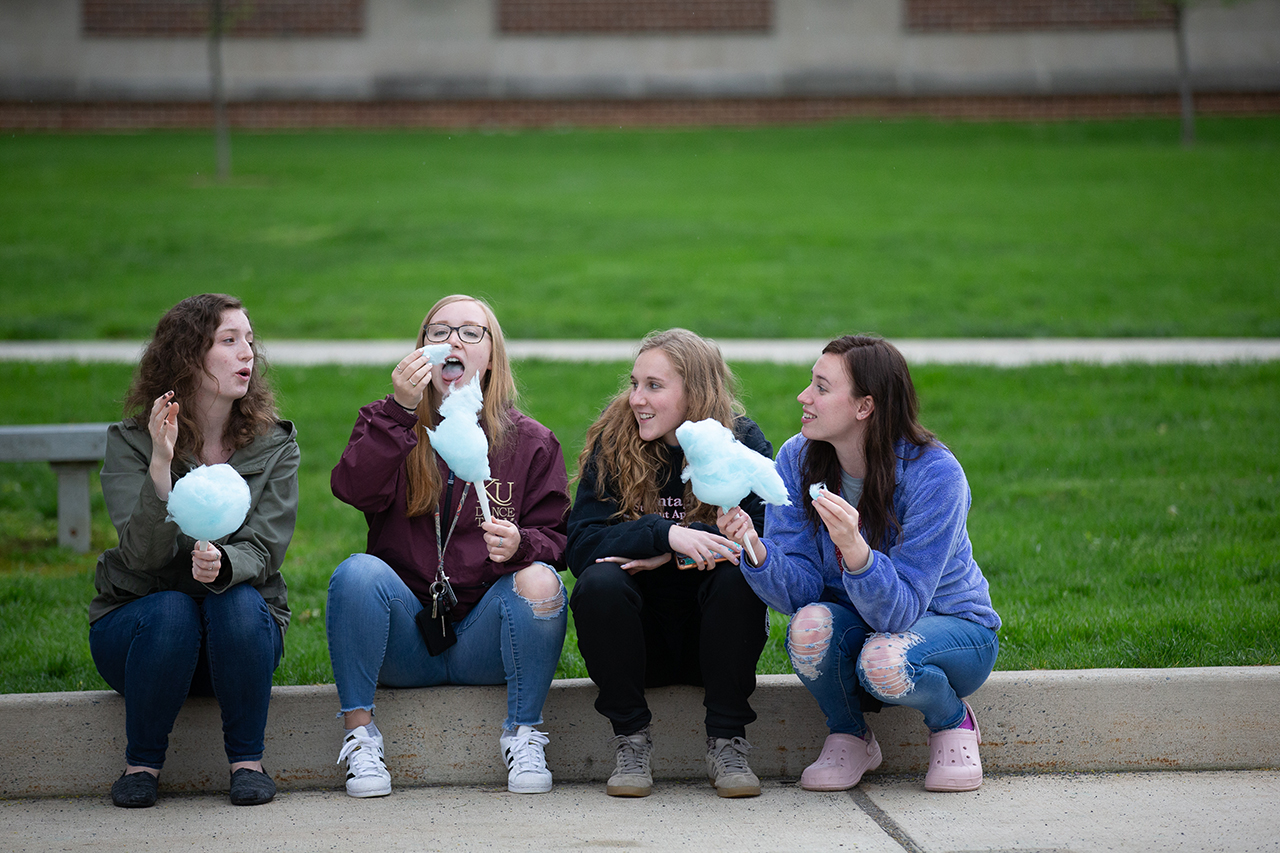 students sitting on a curb eating cotton candy