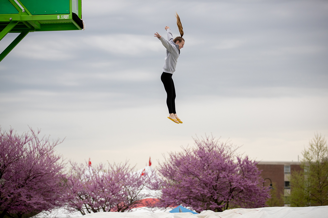 "student jumping off of a platform into a giant cushion on the ""stunt jump"""