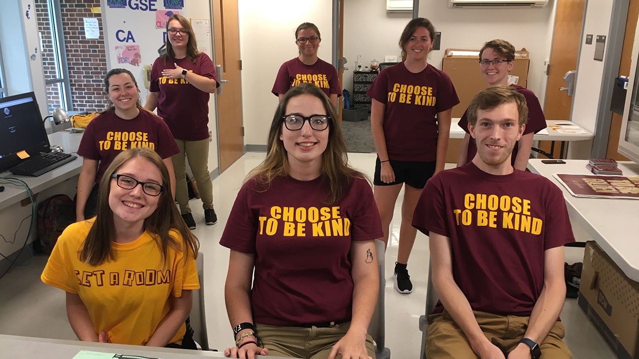 Desk Receptionists pose together behind a Rothermel front desk on move in day