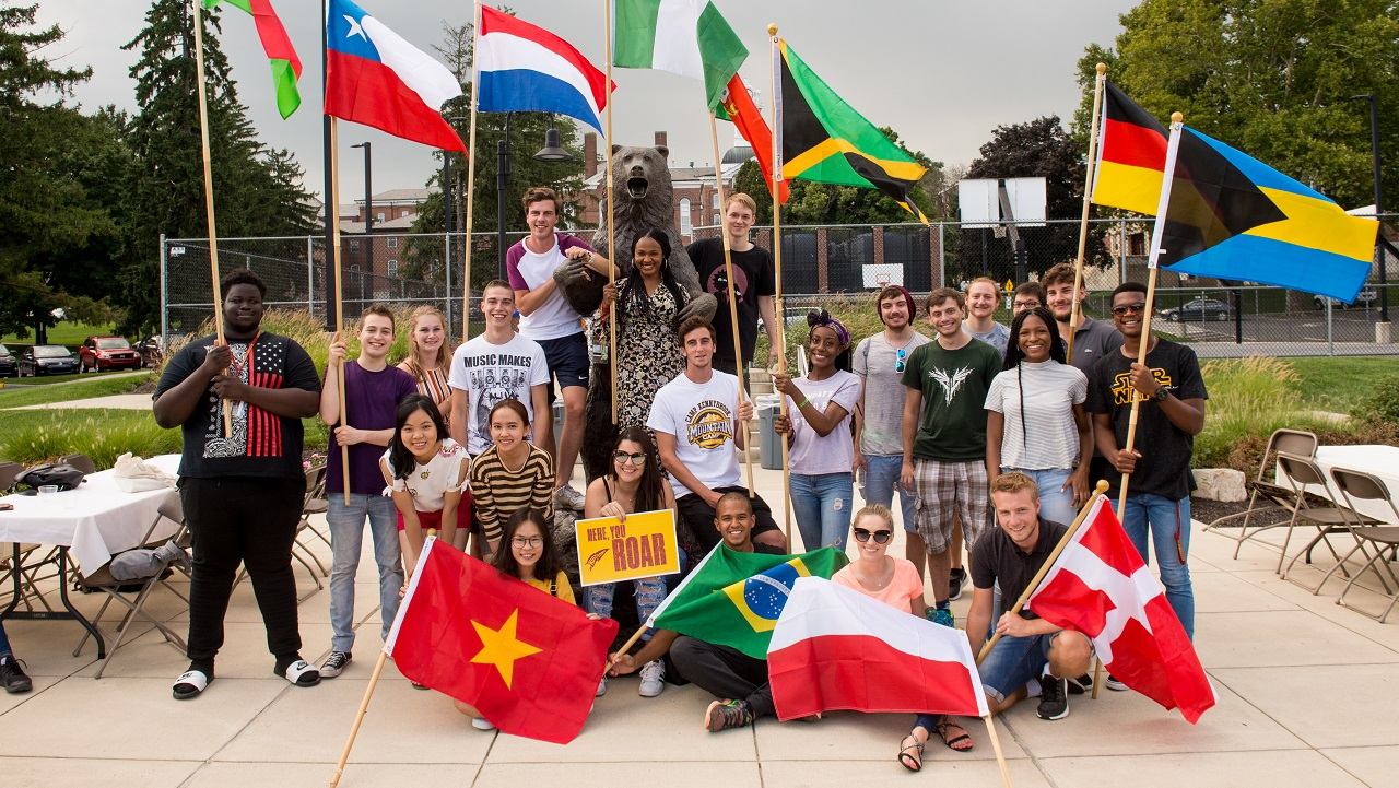 Photo of new international students holding their flags