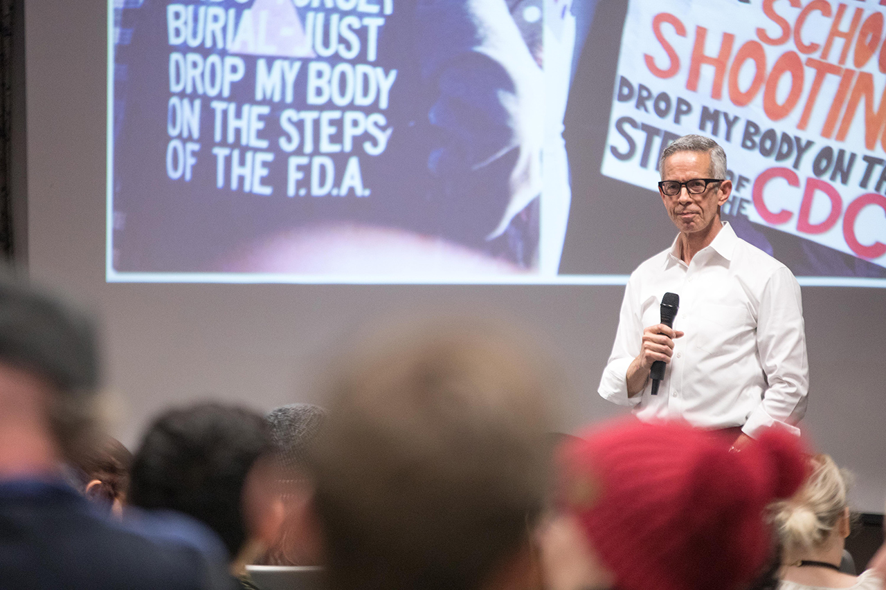 AIDS activist Peter Staley in front of an auditorium of students with a powerpoint displaying images from Act Up