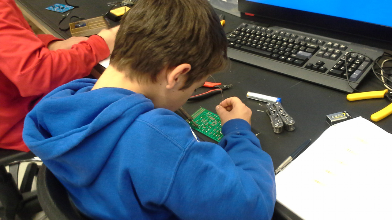 Scouts solder a circut for electronics merit badge.