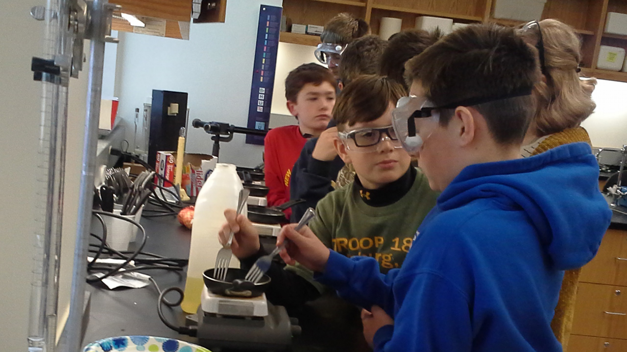 Scouts stir solution over burner for chemistry merit badge.