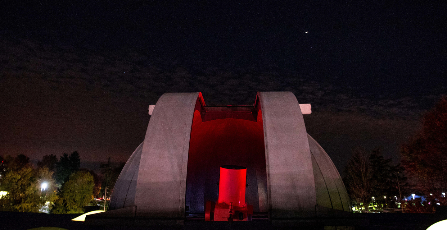 Observatory open at night.  A red light inside the dome reveals the astronomical telescope.