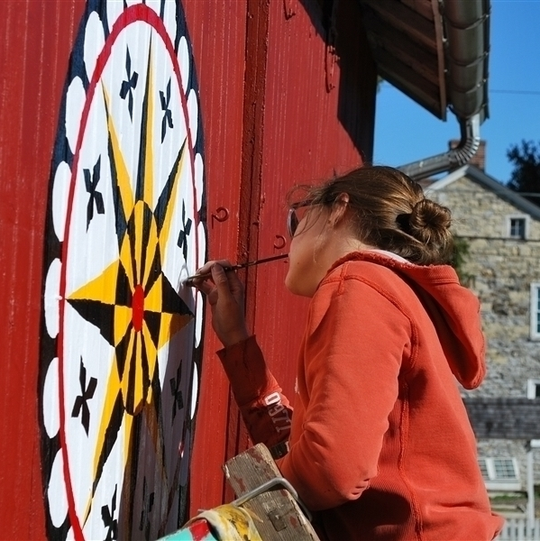 A female identifying student with her head tilted to the right, stands on a ladder painting a yellow, black, white, and red barn star