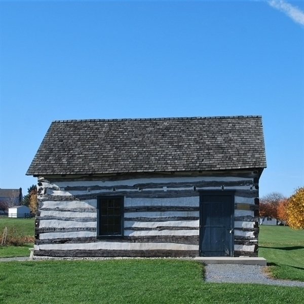 Image of a log cabin with a shingle roof against a blue sky. There is white morter between the hand hewn logs