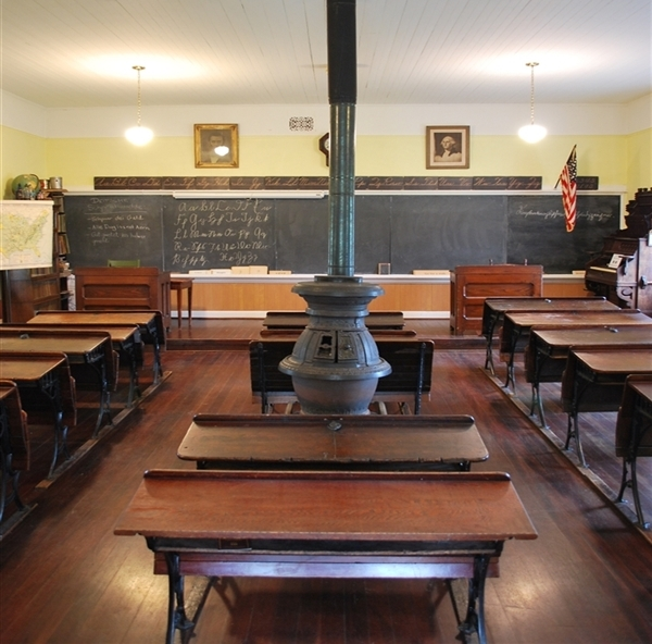 Looking at the slate board at the front of the class from the back of the schoolhouse. Wooden 2-seater desks make three rows facing front.