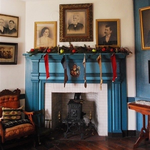 The teal mantle over the white stone fireplace in the parlor is decorated for Christmas
