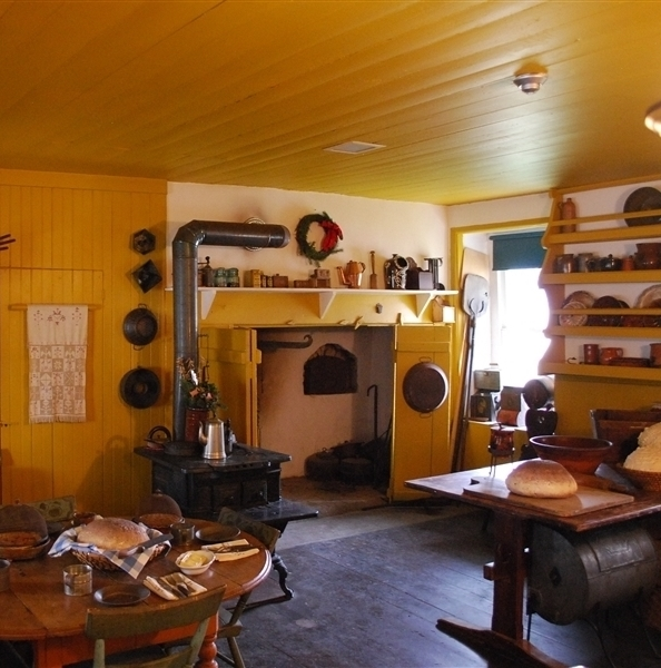 A bright yellow kitchen featuring a hearth, cast iron stove, redware, and other implements on two wooden tables.