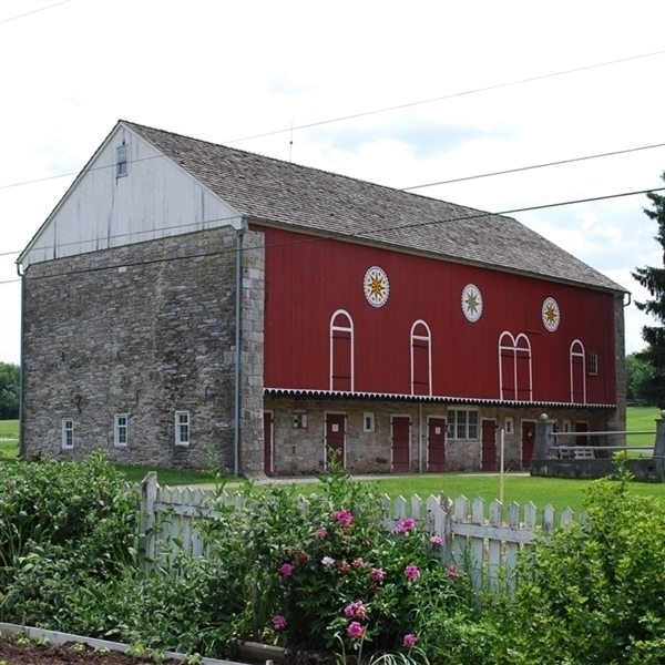 Image of the forebay side of the red and stone bank barn. The barn also has three barn stars painted along the side.