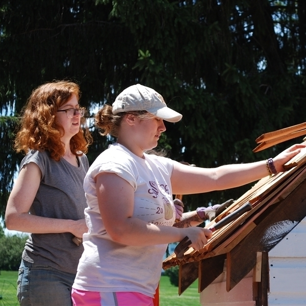 Two female identifying students working together to put on a wooden shingle roof on an outhouse