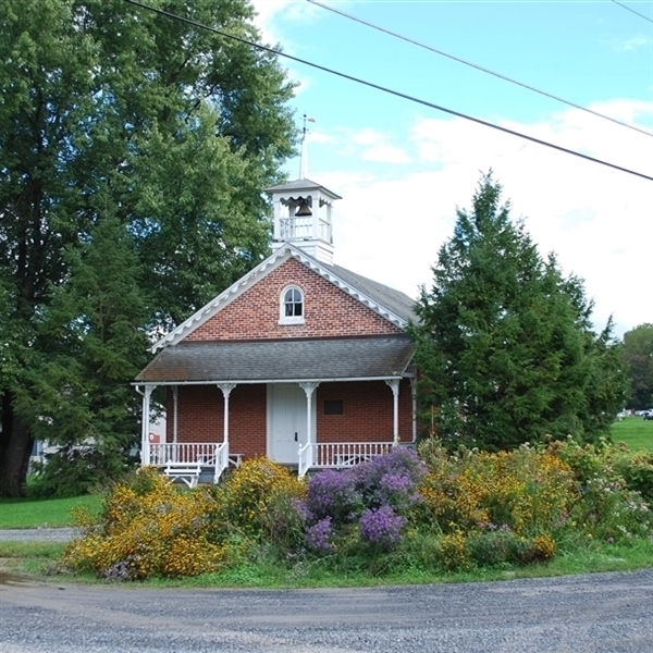 Image of the brick one-room schoolhouse with flowers in the foreground.
