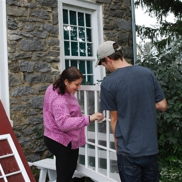 Image of a female identifying student and a male identifying student preparing window sashes for instillation.