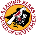 Logo of the Reading Berks Guild of Craftsmen: Yellow background with black Berks County in the middle, with a white and red distelfink bird and stylized tulip.