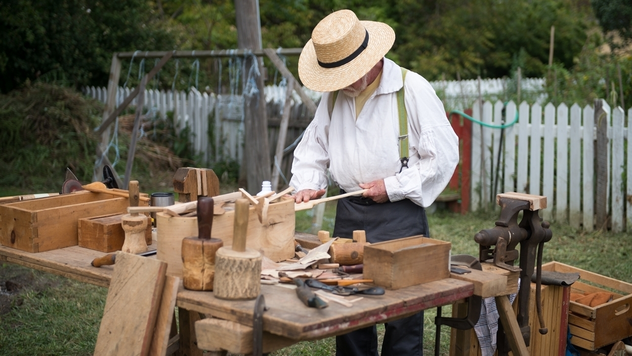 A man with his face covered is looking down at a work bench covered in tools and wood. He is carving spoons.