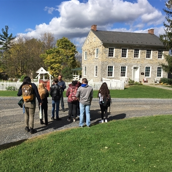 A tour group of students standing in the gravel driveway in front of the house, listening to the tour guide.