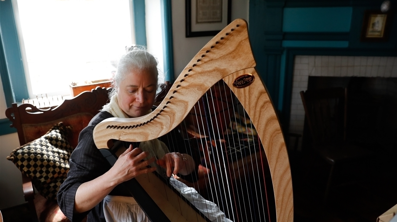 An older woman with white hair playing the harp.