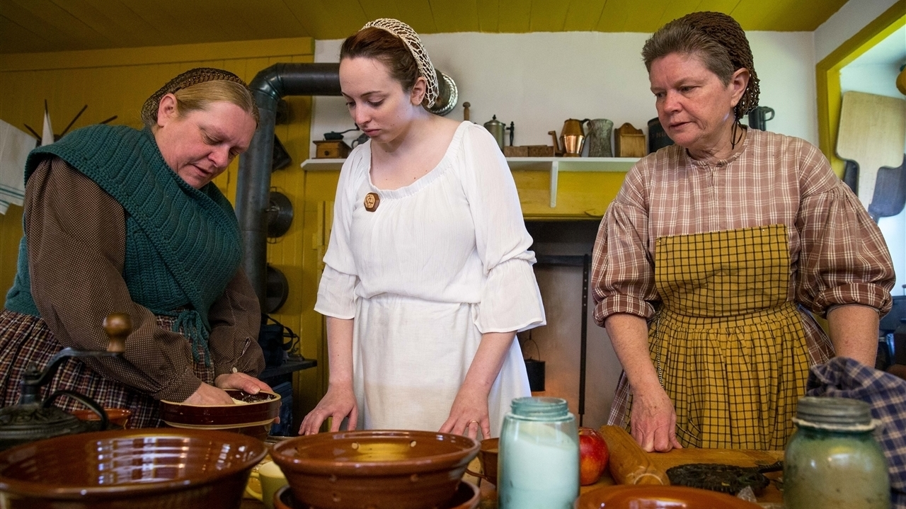 Two middle age women and a young woman cooking wearing traditional clothing.