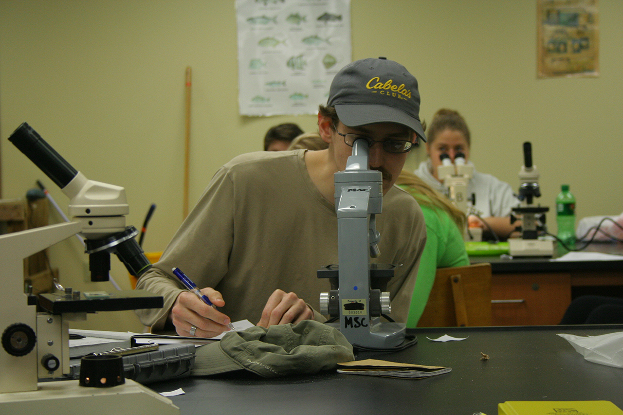 student at a microscope in the lab