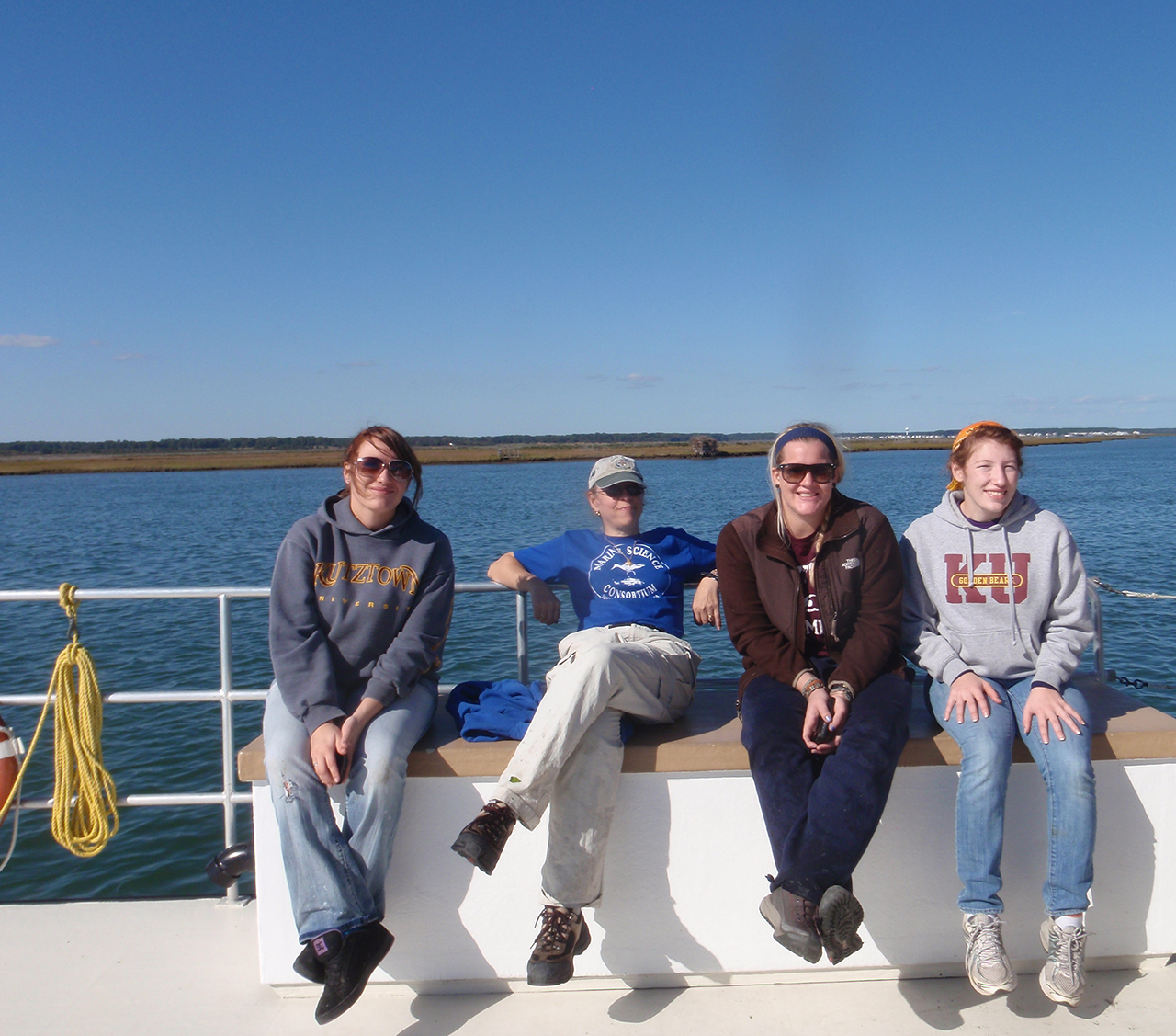 Dr. Ryan and students sitting on a boat with blue skies