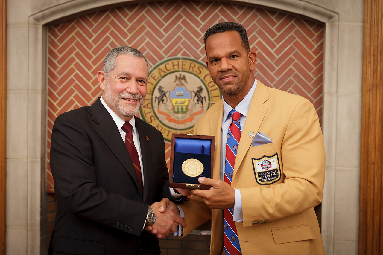 Interm President Dr. Carlos Vargas (left) presents Andre Reed (right) with the President's Medal.
