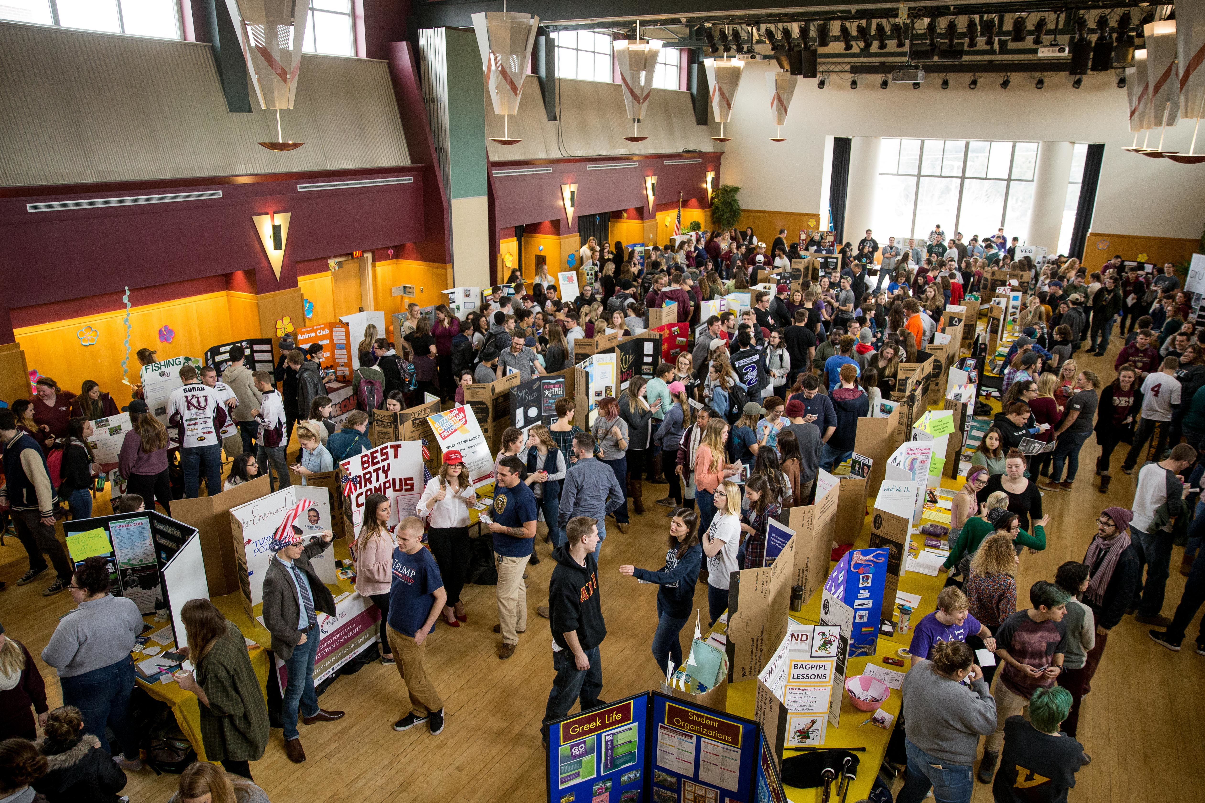 overview photo of large room with many students exploring tables of information about student organizations