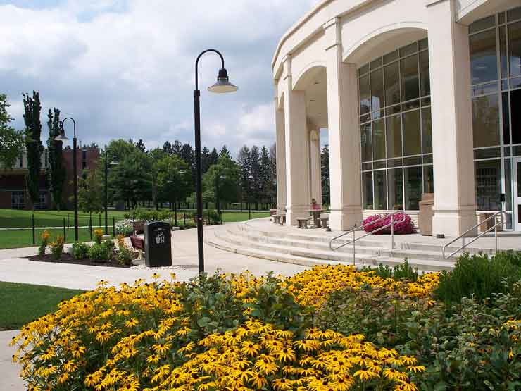 Peering over a flower bed of black-eyed Susans is a right view of the Academic Forum, stairway, pillars and glass front.