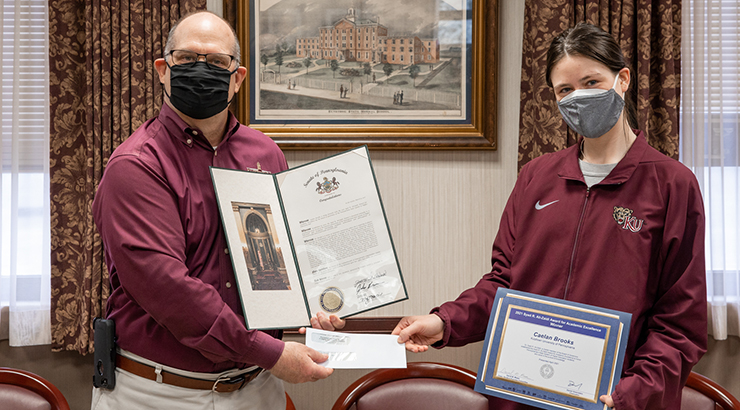 President Hawkinson, left in image, presents Caelan Brooks, right with the 2021 Syed R. Ali-Zaidi Award for Academic Excellence.