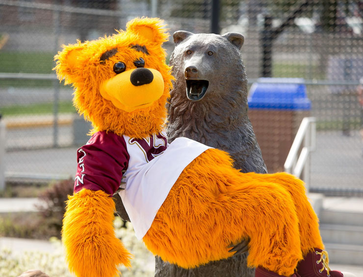 Avalanche mascot in the arms of the bronze Golden Bear statue.