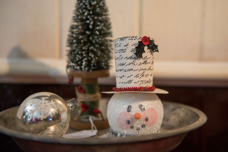 Three ornaments, fill a worn silver pie plate: a Styrofoam snowman's head wearing a white top hat with illegible script on the hat, a silver ball with a white etched snowflake and a Christmas tree atop a yarn spool.