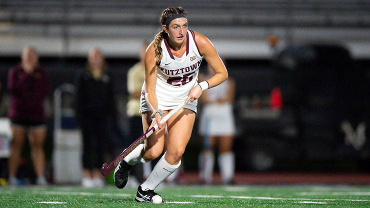Mackenzie Fuhrman, playing field hockey on Astro-turf in white field hockey uniform with Kutztown in maroon letters.