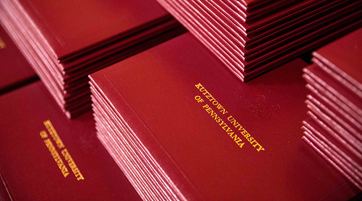diploma holders with the words KUTZTOWN UNIVERSITY OF PENNSYLVANIA embossed in gold.