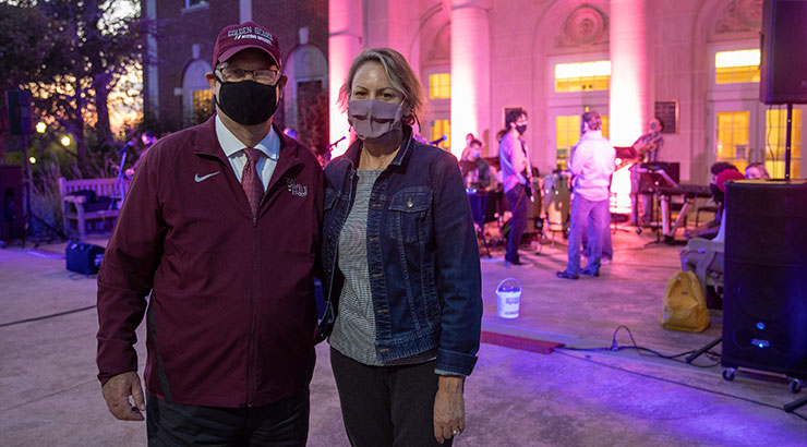 President and Mrs. Hawkinson stand outside an illuminated Schaeffer Auditorium during a student music event.