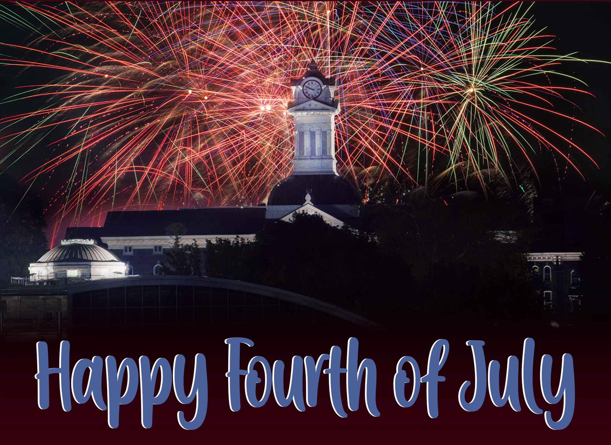 Fireworks illuminate the night sky with Old Main's clocktower in the foreground. The words Happy Fourth of July is written in bold, blue across bottom of image.