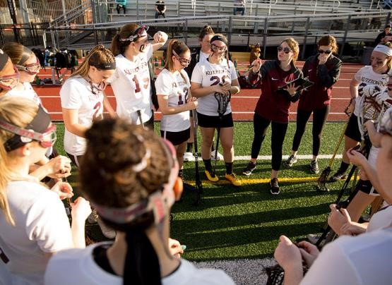 Kutztown University's women's lacrosse team gather around head coach, Jackie Stezzi as she gives instruction on the side line during a time out.