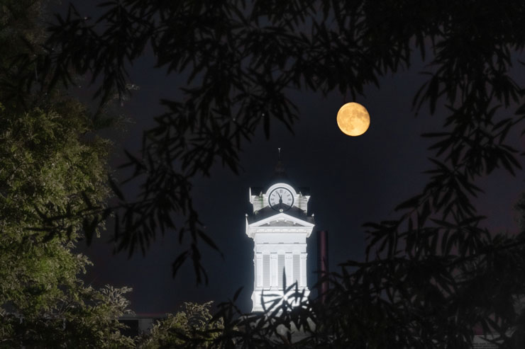 KU clock tower lit up at night with a full moon in the sky above it.