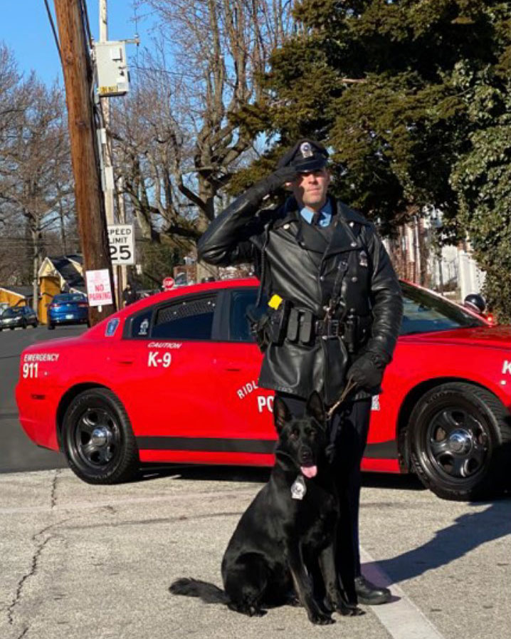 Photo of Matt Rowan '06 with his black K-9 dog in front of his red police car.