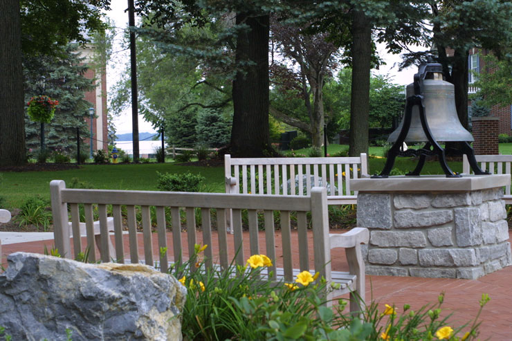 Summer scene at Memorial Bell Plaza. Bell is surrounded by park benches with boulders and gold lilies behind each bench. In the background is lush green grass in the shade of towering trees.